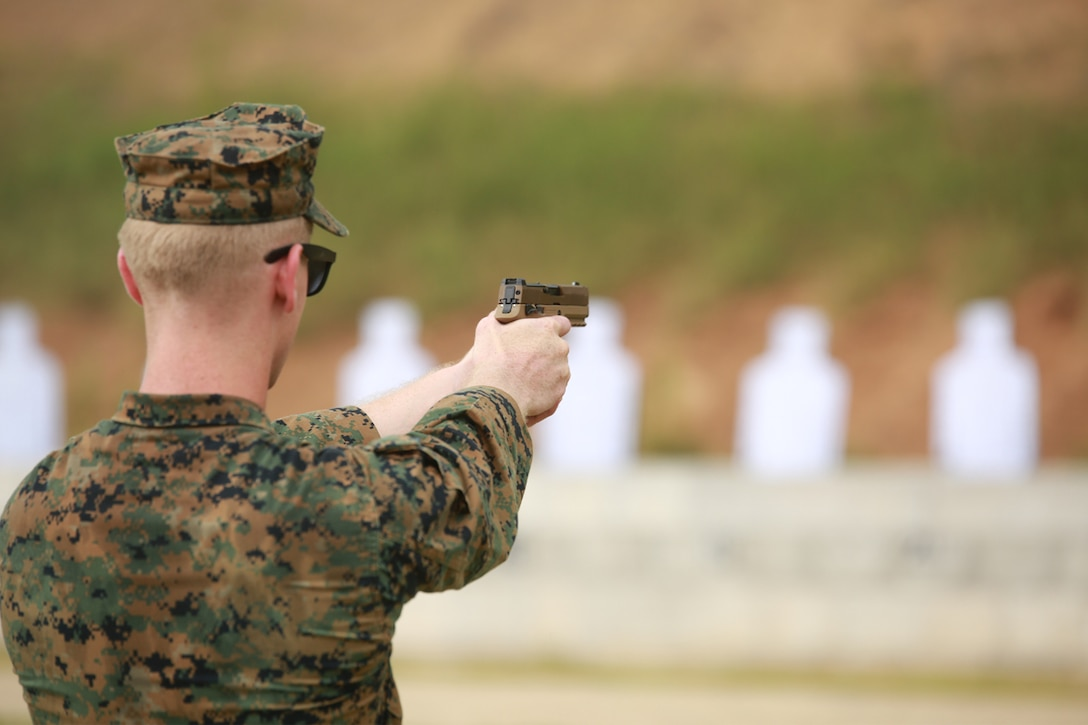 A Marine instructor shoots the M18 Modular Handgun System at a firing range during Instructor and Key Personnel Training, June 25, aboard Marine Corps Base Quantico, Virginia.