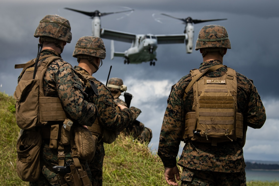 U.S. Marines observe an MV-22B Osprey prepare to land during a simulated embassy reinforcement, organized by Pre-Deployment Training Branch, III Expeditionary Operations Training Group, III Marine Expeditionary Force Information Group at Kin, Okinawa, Japan, Sept. 12.