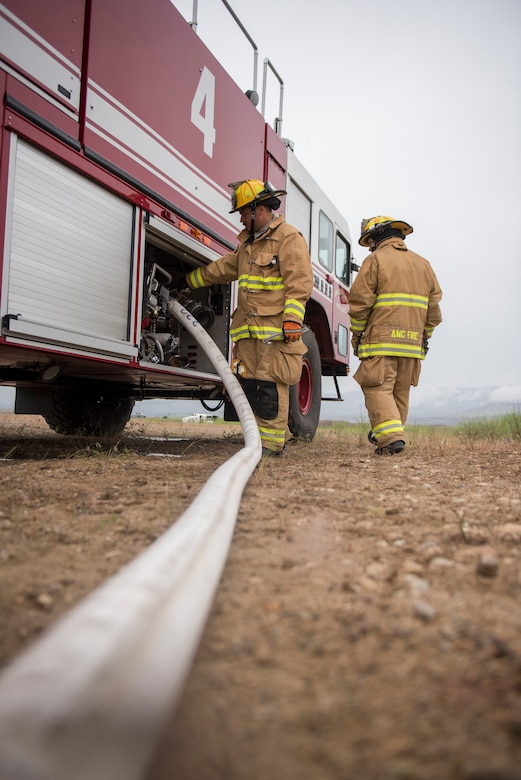 A fire hose runs from the left corner of the picture, leading the viewer to a red fire truck where two fire fighters wearing their brown fire suits, with yellow reflective stripes, and helmets turn the water on for the hose.