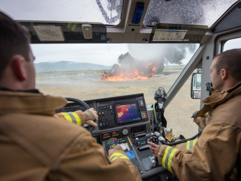 Two male fire fighters in their brown and yellow fire suits sit inside a fire truck that is overlooking a fire with billowing black smoke. Inside the cab of the fire truck is an infrared screen showing the heat from the fire.