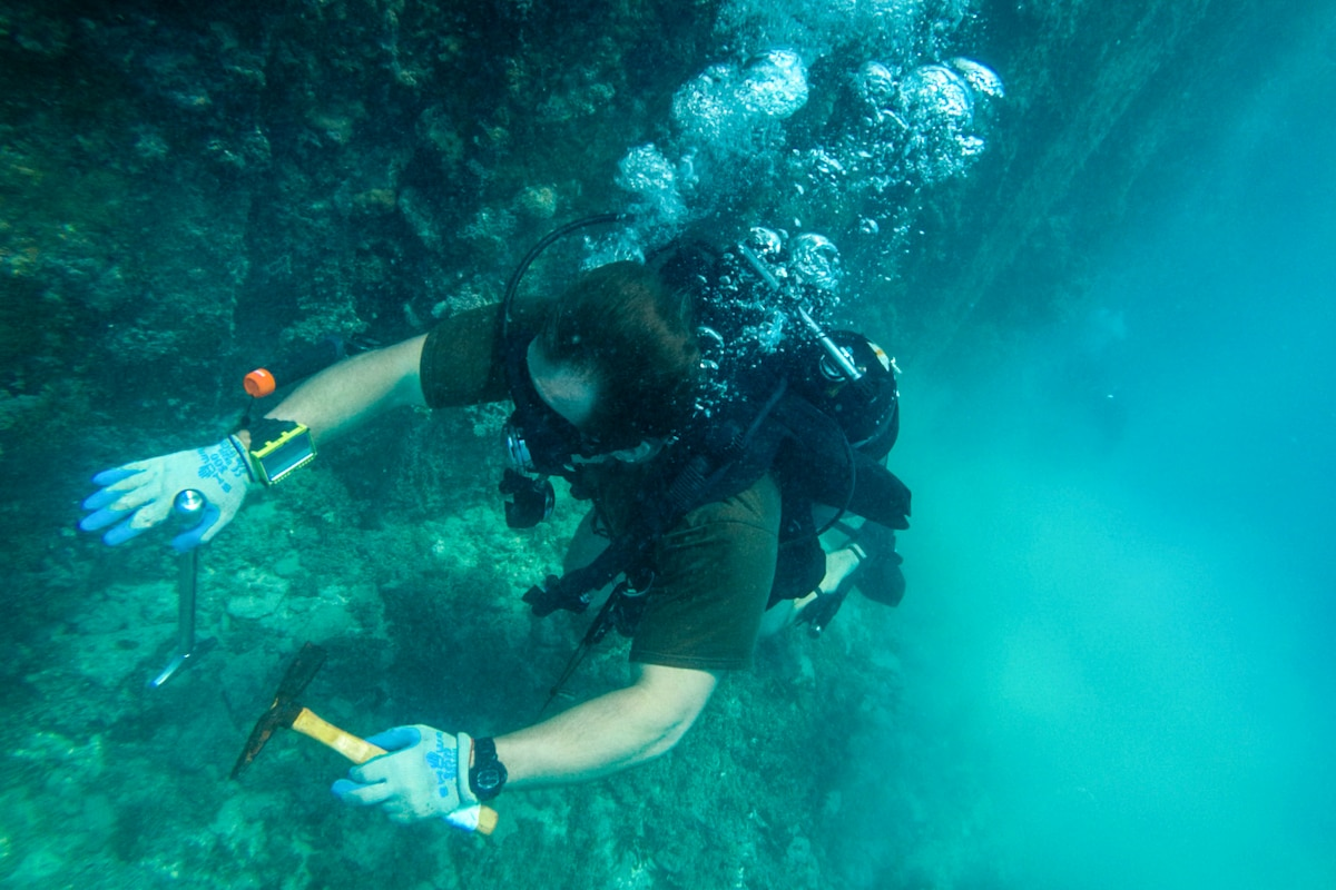 A sailor in dive gear holds tools while working on a structure underwater.
