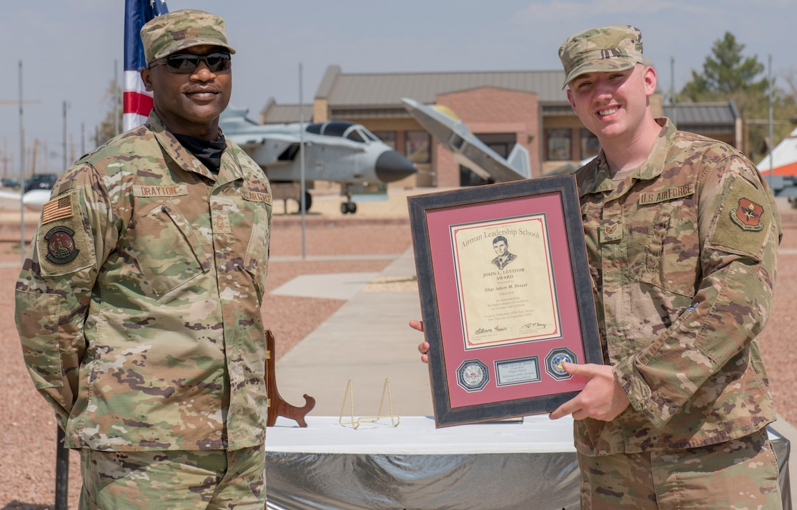 Staff Sgt. Adam Reszel, right, assigned to the 49th Equipment Maintenance, accepts the John L. Levitow award during the graduation of ALS class 20-6, Sept. 22, 2020, on Holloman Air Force Base, New Mexico. The Levitow award is presented to the student demonstrating the highest level of leadership and scholastic performance, and is partially determined by the assignment of points by their peers. (U.S. Air Force photo by Airman 1st Class Quion Lowe)