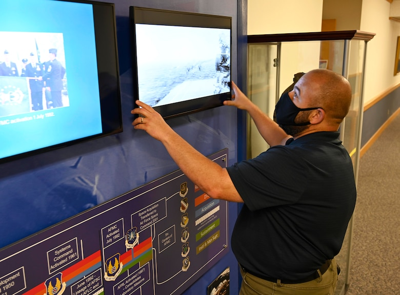 Jack Waid, Air Force Materiel Command Historian, sets up one of the information screens on the history display at the AFMC Headquarters, Wright-Patterson Air Force Base, Ohio. (Air Force photo by Darrius Parker)