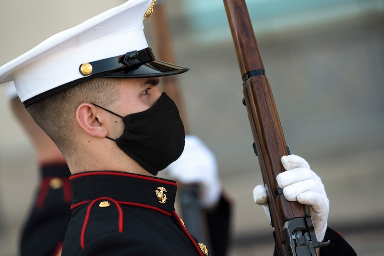 A service member wearing a mask holds a weapon.