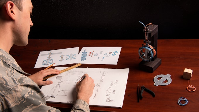 Senior Airman Hartman, 726th Air Command Squadron cyber transport technician, sketches an idea for his invention of a cable management system, Sept. 16, 2020, at Mountain Home Air Force Base, Idaho. Hartman started with sketches and moved to digital modeling and 3D printing as way to communicate the benefits and viability of his device to senior wing leadership. (U.S. Air Force photo by Senior Airman Andrew Kobialka)