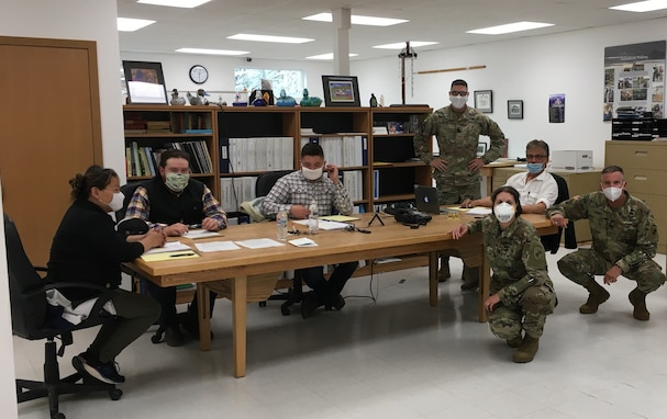 """U.S. Army Reserve Lt. Col. Hugh Dougalas, governance and participation section chief (center left), Capt. Sarah Robinson, public health nurse (center right), Col. Bradford """"Brad"""" Hughes, functional specialty team chief (right), and members of the Qawalangin Tribe (Q-Tribe) council pose while participating in a council meeting during an Innovative Readiness Training Civil-Military Partnership Leader's Reconnaissance, Unalaska, Alaska, July 23, 2020.  IRT is a joint training concept that the Department of Defense (DOD) implemented to increase unit deployment readiness, leveraging the military contributions of U.S. Armed Forces capabilities, combined with local resources to build strong civil-military partnerships for communities in the contiguous United States and its territories."""