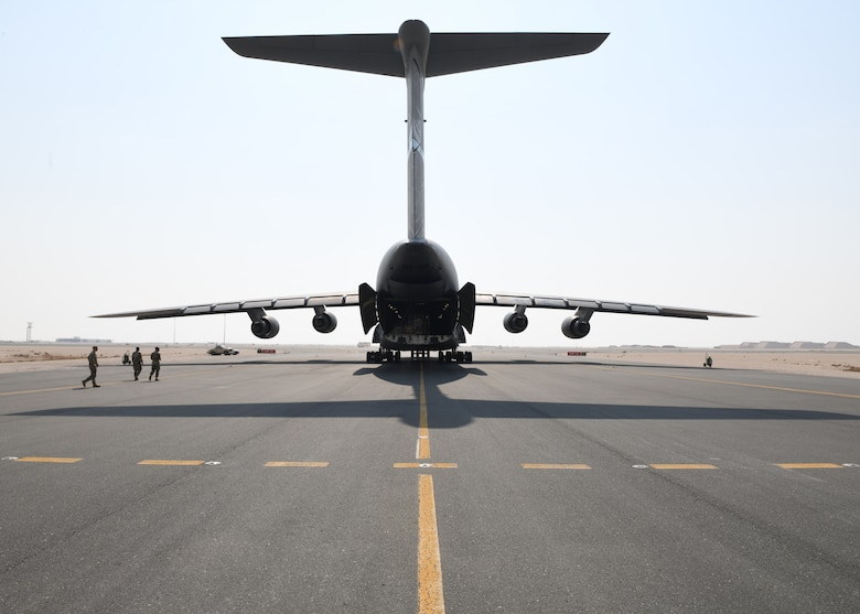 A C-5 Galaxy sits on the flight line of Al Udeid Air Base, Qatar, Sept. 18, 2020, to deliver a specialized medical container designed to transport individuals with infectious diseases. The Negatively Pressurized Conex, or NPC, is configured for the C-17 Globemaster III and C-5 Super Galaxy aircraft to safely transport up to 28 passengers or 23 patients, including ambulatory and litter, around the globe. (U.S. Air Force photo by Staff Sgt. Kayla White)
