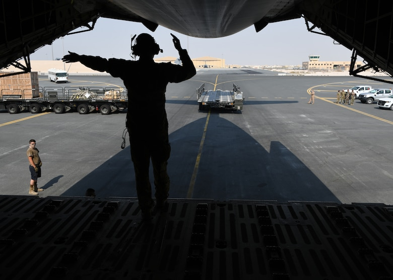 Airman 1st Class Taylor Robinson guides a Tunner 60K Loader toward a C-5 Galaxy on the flight line of Al Udeid Air Base, Qatar, Sept. 18, 2020, to off load a specialized medical container designed to transport individuals with infectious diseases. The Negatively Pressurized Conex, or NPC, is configured for the C-17 Globemaster III and C-5 Super Galaxy aircraft to safely transport up to 28 passengers or 23 patients, including ambulatory and litter, around the globe. (U.S. Air Force photo by Staff Sgt. Kayla White)