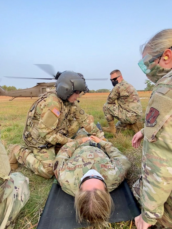 A Critical Care Flight Paramedic assigned to the 2-211 General Aviation Support Battalion, Minnesota Army National Guard ensures a patient is ready for transportation during medical evacuation training with the 148th Fighter Wing, Minnesota Air National Guard, at Camp Ripley Training Center, Minnesota on Saturday, September 20, 2020.