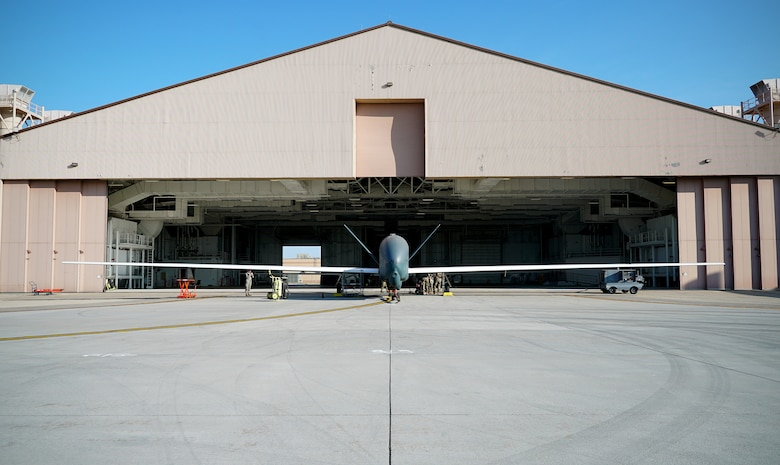 A small unmanned aircraft is shown in center frame in front o f an open hangar, with its wingspan shown in entirety from left to right of the picture.