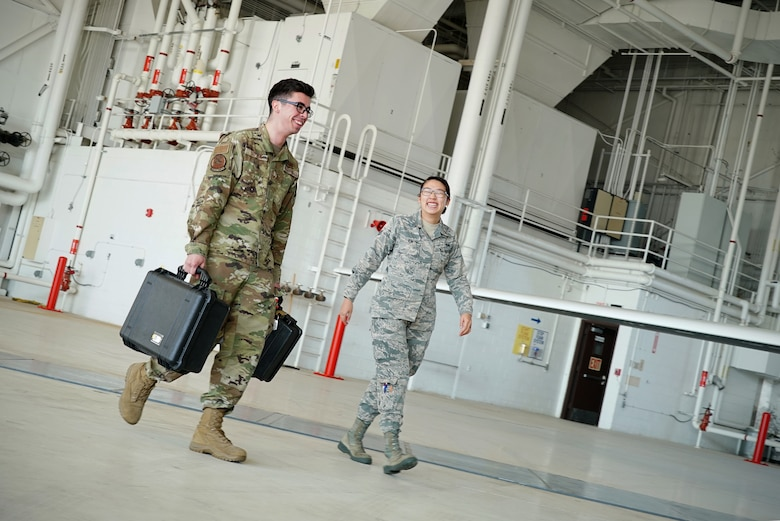 A military-uniformed man and woman walk through a large aircraft hangar next to each other as they smile in conversation.