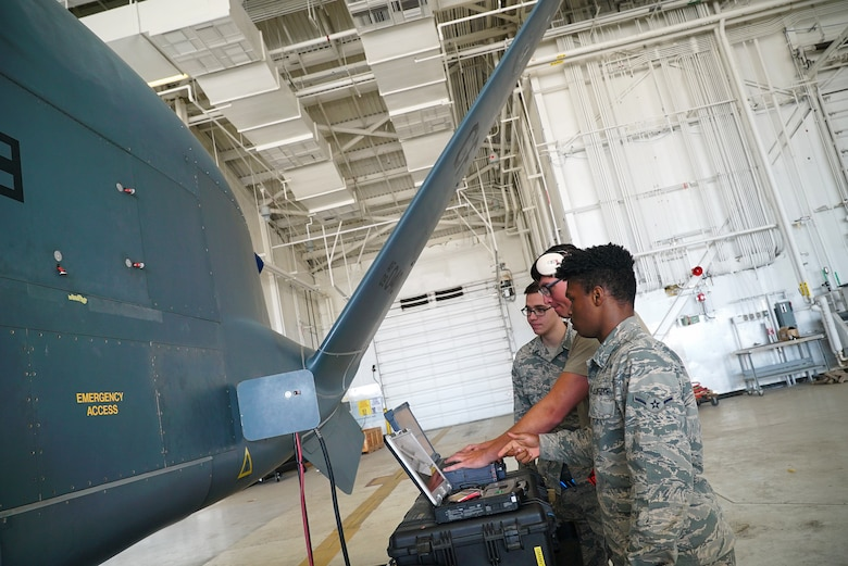 The side of a small unmanned aircraft is shown on the left-hand side of the frame, as three uniformed military members stand near it with a laptop in front of them.