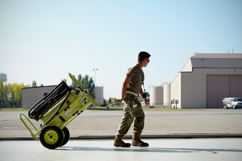 A uniformed military member walks across the frame with a large neon yellow wheeled fire extinguisher in tow.