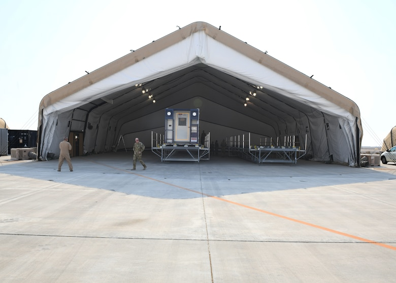 A specialized medical container designed to transport individuals with infectious diseases sits in a clamshell hangar on the flight line of Al Udeid Air Base, Qatar, on Sept. 18, 2020. The Negatively Pressurized Conex, or NPC, is configured for the C-17 Globemaster III and C-5 Super Galaxy aircraft to safely transport up to 28 passengers or 23 patients, including ambulatory and litter, around the globe. (U.S. Air Force photo by Staff Sgt. Kayla White)