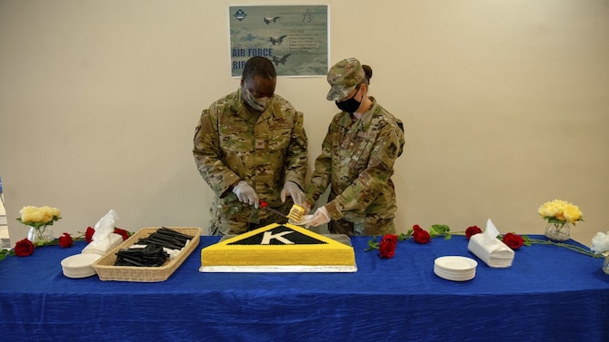 U.S. Air Force Col. Miles McClung, the 379th Air Expeditionary Wing vice commander, cuts into a special-made Triangle K cake, a nod the Wing's heritage, on Sept. 18, 2020, at Al Udeid Air Base, Qatar. AUAB personnel enjoyed a wide variety of COVID-compliant activities to help them connect and celebrate the Air Force's 73rd birthday. (U.S. Air Force photo by Staff Sgt. Heather Fejerang)