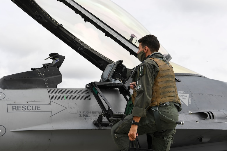 U.S. Air Force Capt. Timothy Joubert, 555th Fighter Squadron chief of mobility, climbs into a U.S. Air Force F-16 Fighting Falcon at Aviano Air Base, Italy, Sept. 24, 2020. Airmen and U.S. Air Force F-16 Fighting Falcons assigned to the 555th FS participated in exercise Brave Warrior 20 alongside Hungarian, Slovakian, and Romanian partners. During the exercise 555th FS aircraft will perform close air support with Hungarian, Slovakian, and Romanian coalition ground forces and receive fueling from Hungarian Defense Force logistics personnel at Papa Air Base, Hungary. (U.S. Air Force photo by Staff Sgt. Savannah L. Waters)