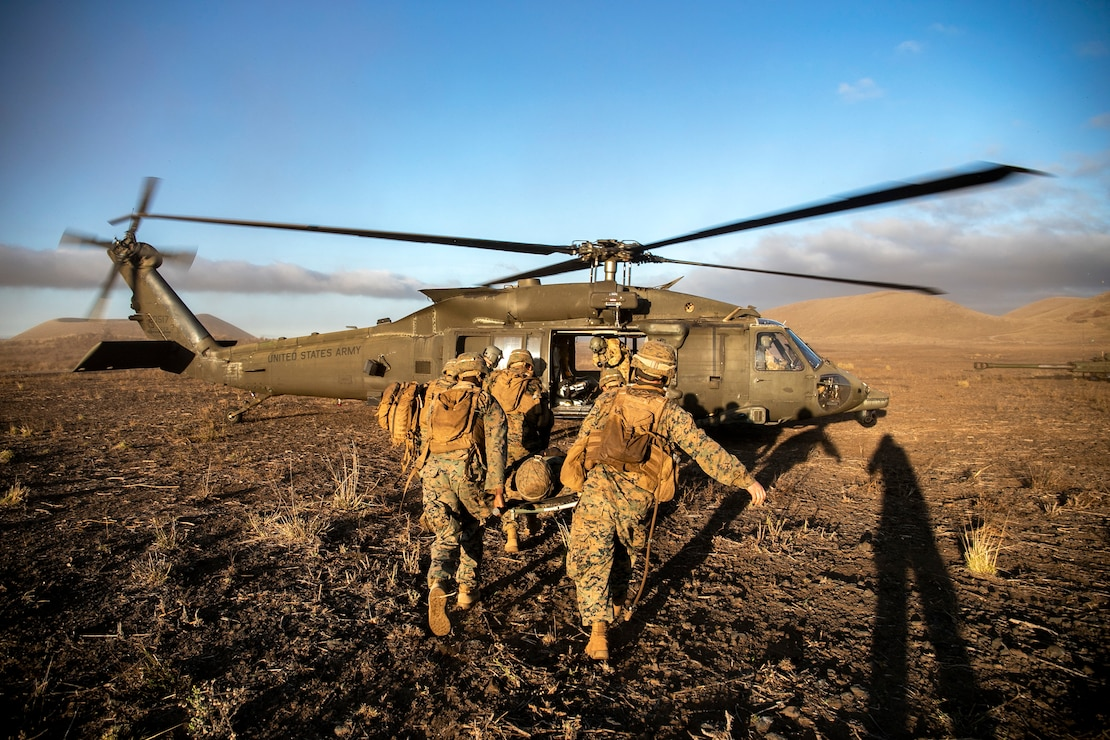 U.S. Marines and a U.S. Navy corpsman prepare to load a simulated casualty onto a U.S. Army UH-60 helicopter during a casualty evacuation drill aboard Pohakuloa Training Area, Hawaii, Sept. 20.