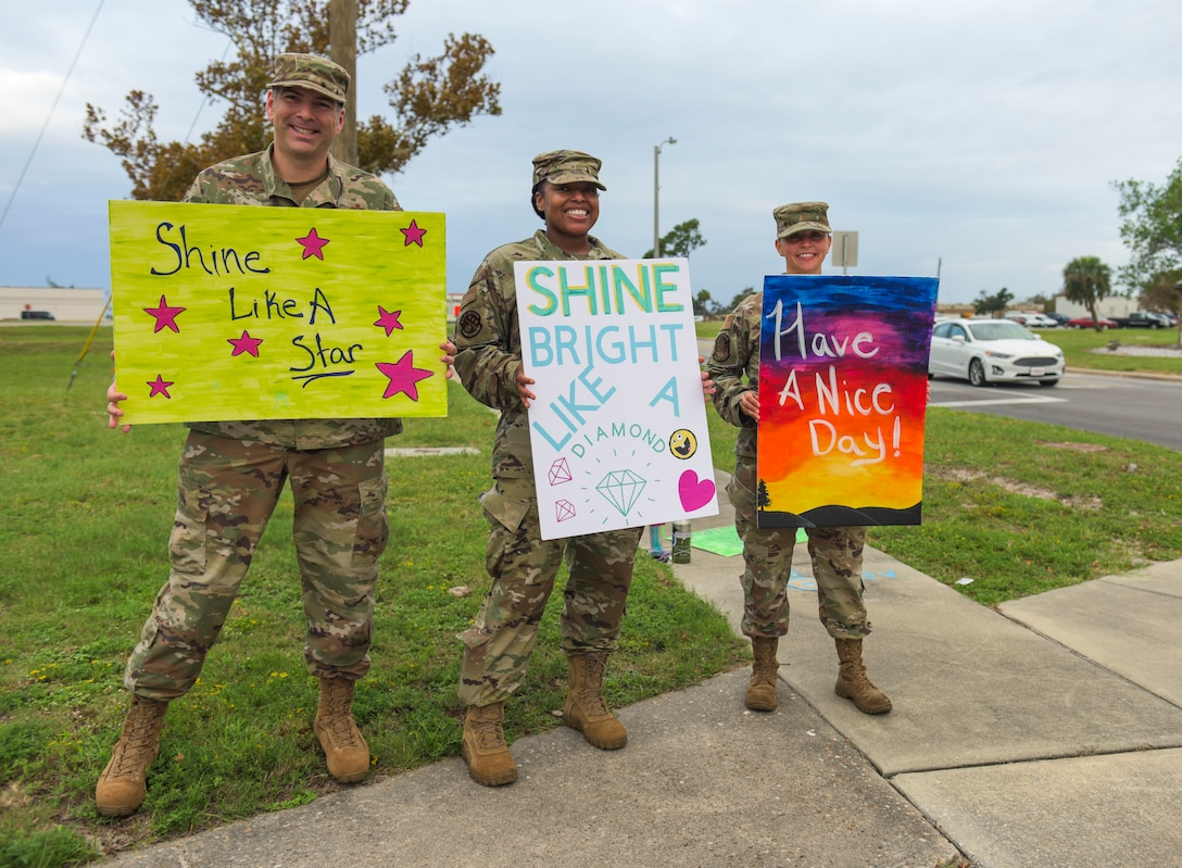 U.S. Air Force Master Sgts. James Fisher with the 325th Civil Engineer Squadron, superintendent, left, Charlene Rockett with the 325th Communications Squadron, first sergeant, center, and Moriah Washburn with the 325th Contracting Squadron and 325th CE, first sergeant, right, wave handmade signs near the inbound lane at Tyndall Air Force Base, Florida, Sept. 24, 2020. Tyndall's first sergeants converged near the base's entry gates to wave morale and resiliency signs at passersby. (U.S. Air Force photo by Staff Sgt. Magen M. Reeves)