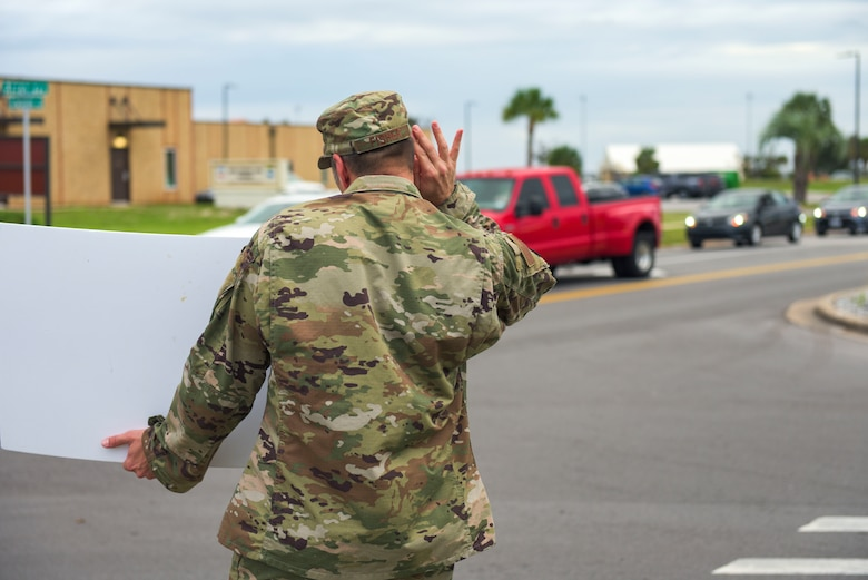U.S. Air Force Master Sgt. James Fisher with the 325th Civil Engineer Squadron, superintendent, waves a handmade sign near the inbound lane at Tyndall Air Force Base, Florida, Sept. 24, 2020. Fisher was part of a group effort fronted by Tyndall's first sergeants to pump up morale on base. (U.S. Air Force photo by Staff Sgt. Magen M. Reeves)