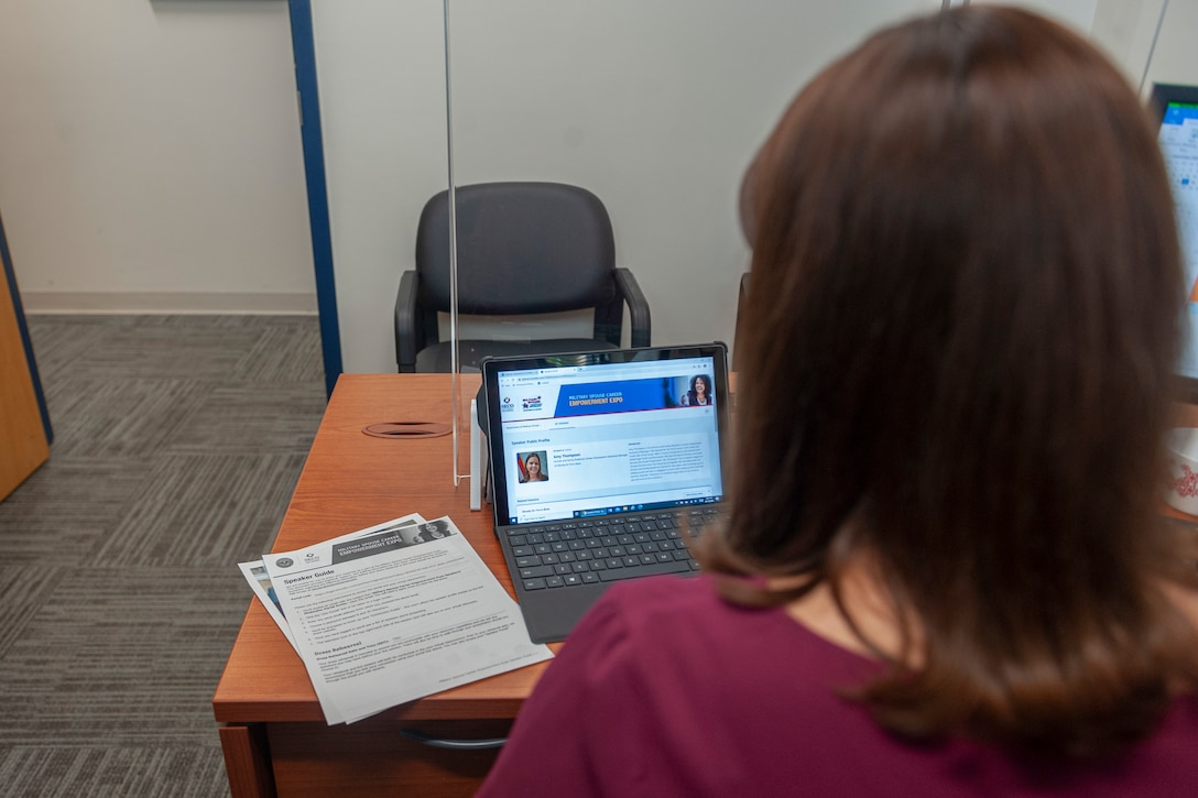 Photo of a woman looking at a laptop screen.