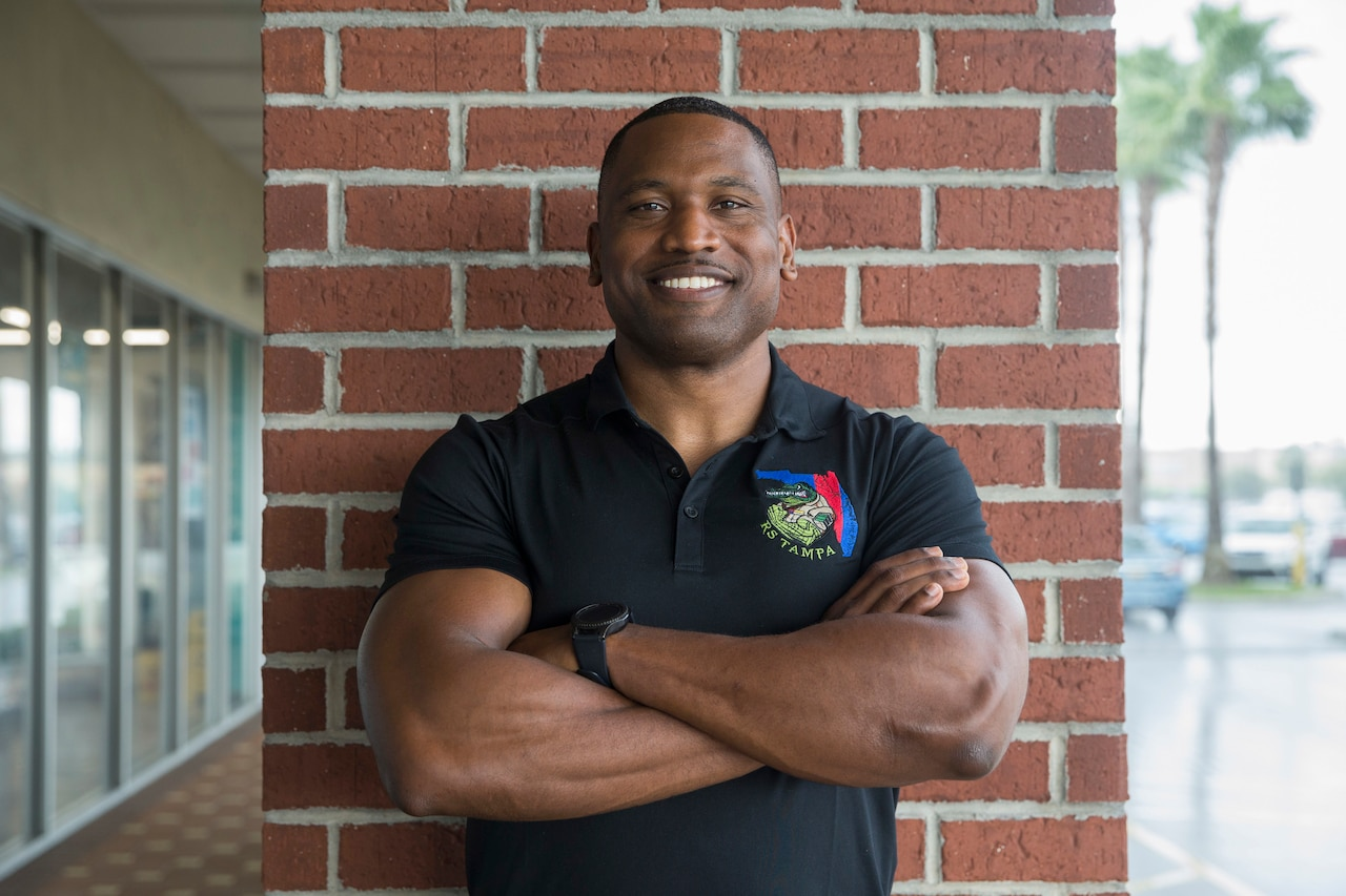 A Marine in  a black polo-style recruiting shirt stands and smiles for a photo with his arms crossed.