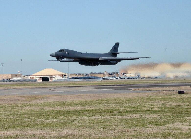 B-1 aircraft in flight above runway