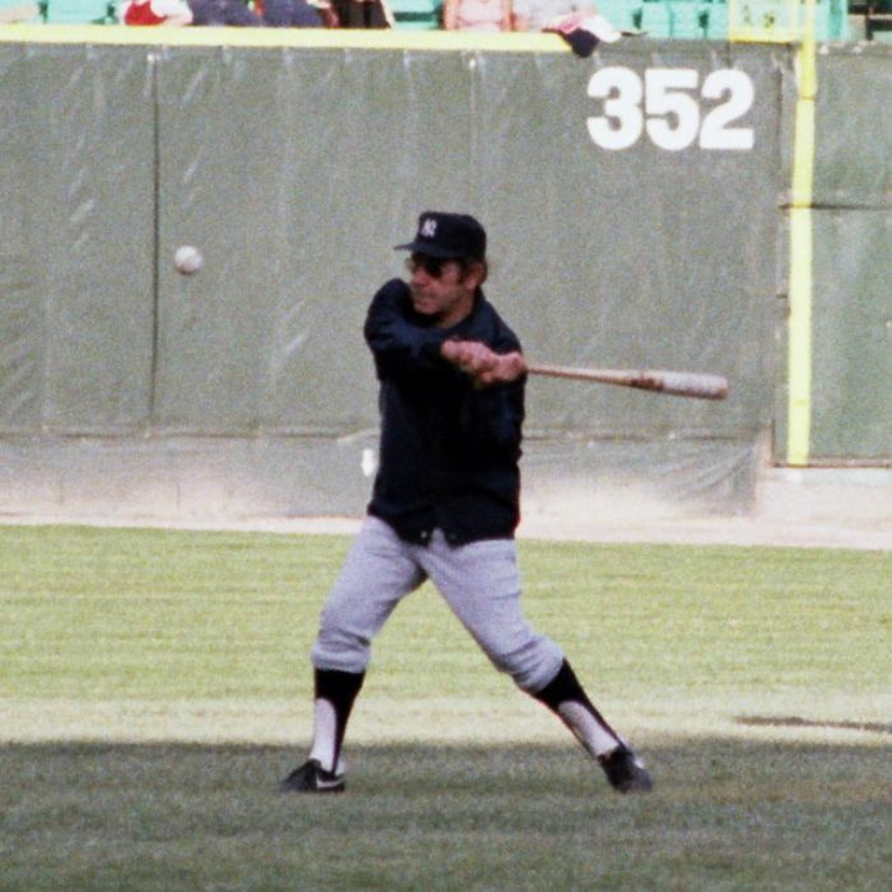A baseball coach swings at a ball.