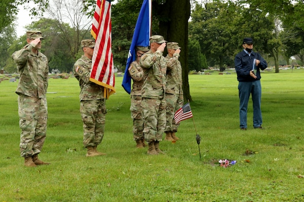 Members of a Wisconsin National Guard color guard with Battery C, 1st Battalion, 120th Field Artillery, salute during a headstone dedication ceremony for Staff Sgt. Walter A. Schaller Sept. 10, 2020, at Holy Cross Cemetery in Milwaukee. Schaller joined the Wisconsin Army National Guard's 32nd Division on April 29, 1941, and was killed in New Guinea on Feb. 20, 1944. He was buried in an unmarked grave at the cemetery in 1949 until a local historian discovered it through research.