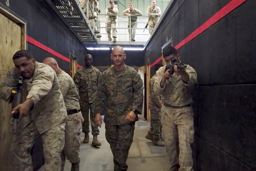A group of Marines walk down a wide hallway carrying guns.