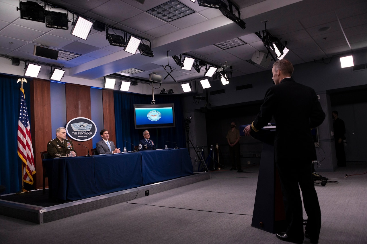 Three Defense Department leaders sit at a table and another person stands at a lectern  in a briefing room.