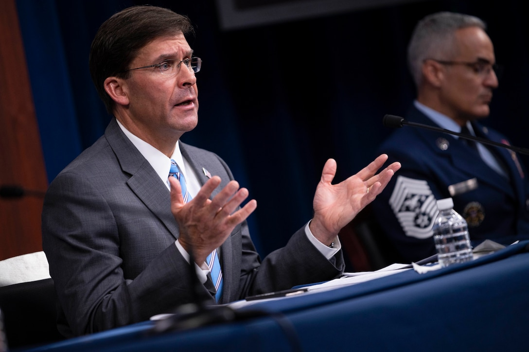 Defense Secretary Dr. Mark T. Esper gestures while sitting and speaking at the Pentagon.