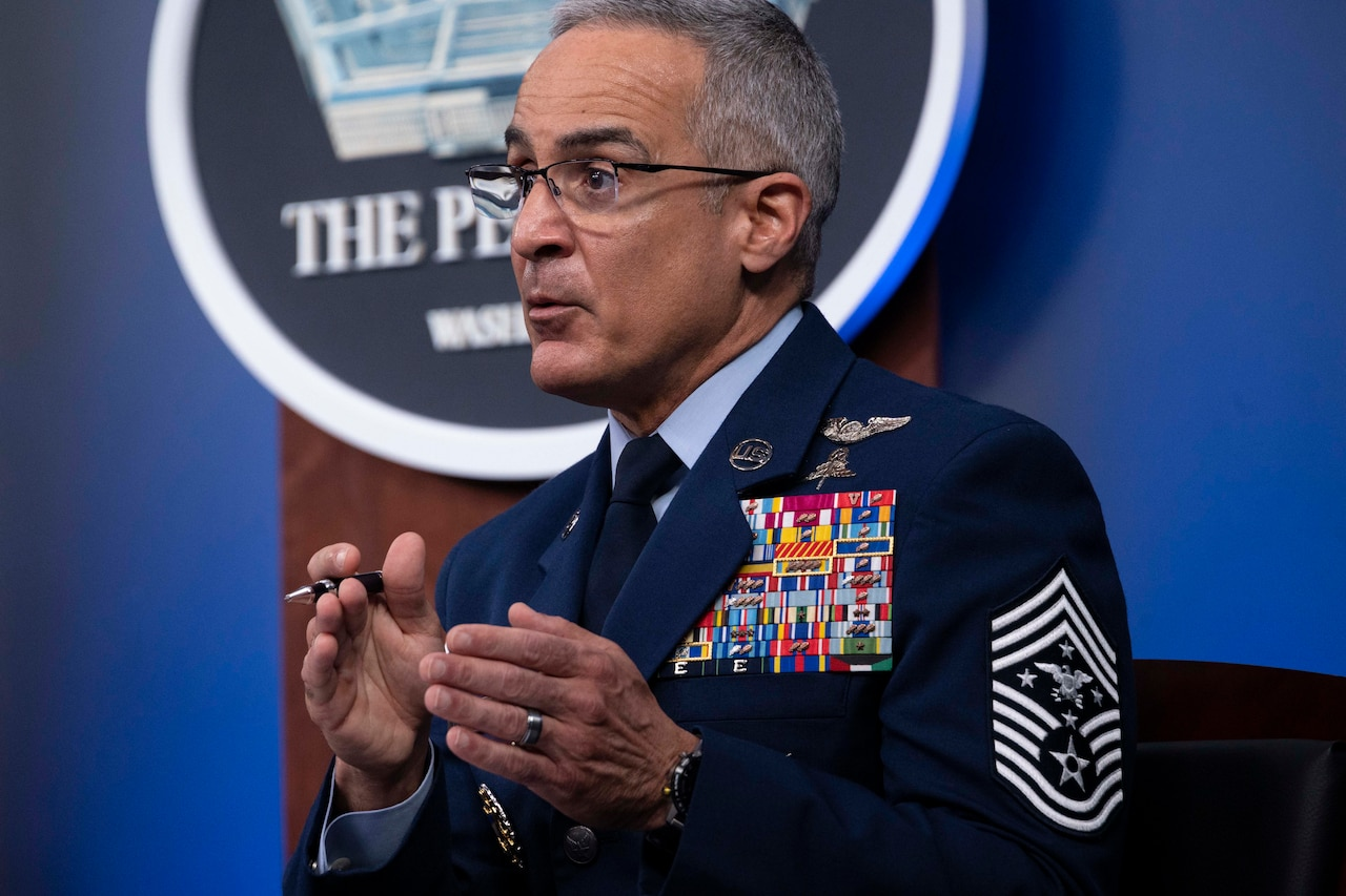 """Senior Enlisted Advisor to the Chairman Ramón """"CZ"""" Colón-López gestures while sitting and speaking at a table."""