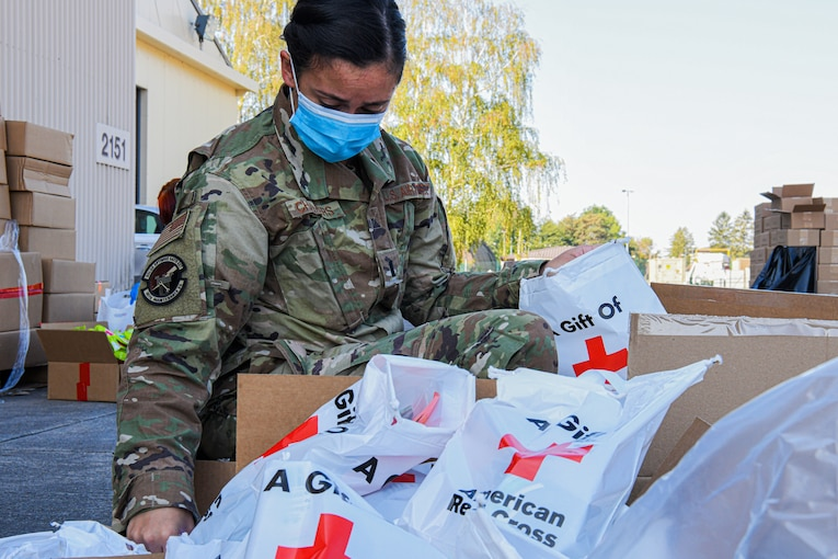 An airman wearing a face mask takes a plastic bag bearing the Red Cross logo out of a box; many other bags with items inside are situated next to the box.