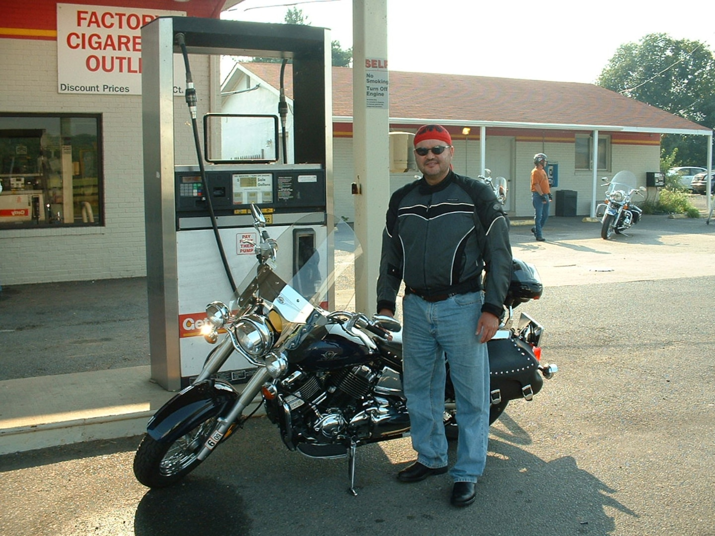 Man stands in front of a tank at a gas station with this motorcycle