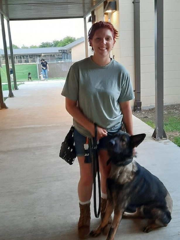 Photo of Airman with German Shepard military working dog by her side.
