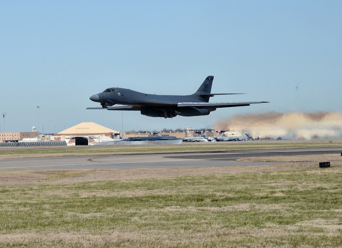 B-1 aircraft in flight above runway