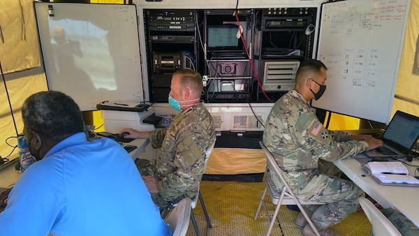 Three men, two in green camo uniforms, sit in a small room with computer equipment.