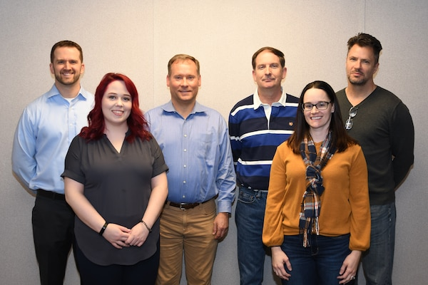 Six members of the Government Furnished Equipment Agnostic Software Team pose for a photo. The 20 member team received the Award of Merit for Group Achievement for their work to deliver quality software products for use in laser weapon systems. Team members include Teresa Berra, James Bohannon, Taylor Evelyn, David Fedorchak, Jr., Donald Fogler, Mark Glass, Kaela Gosdzinski, John Jahn, Thomas Lackert, Jr., James Latourell, Van Le, Jean Levy, Chris Meyer, Melissa Olson-Phipps, David Pritchett, Barry Ross, Eric Schroeder, Zachary Sherrod, Yong Shin, and Elliott Sperlazza. Pictured: FRONT ROW (left to right): Kaela Gosdzinski, Melissa Olson-Phipps BACK ROW (left to right): Eric Schroeder, Mark Glass, Jim Latourell, David Fedorchak Jr.