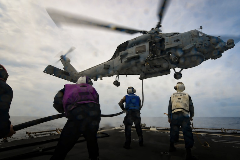 A helicopter hovers as sailors hold a rope aboard a ship.