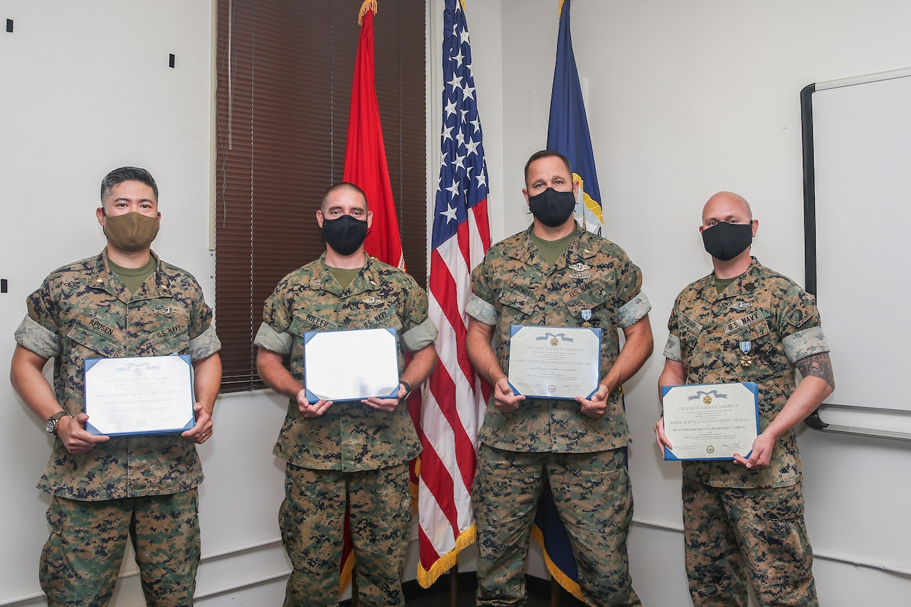 Sailors pose for a photo at an award ceremony.