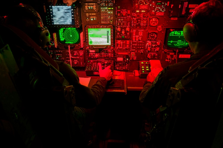 Two airmen sit in front of aircraft controls.