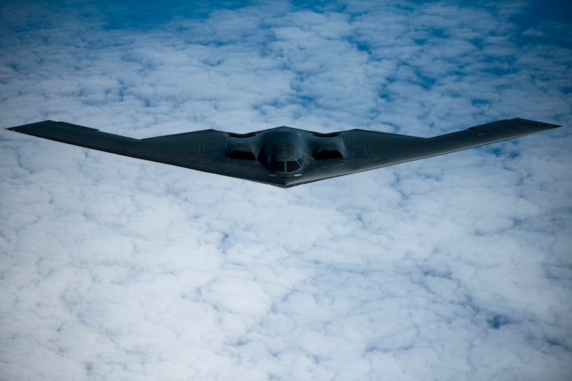 An Air Force B-2 soars in a blue, cloud-specked sky.
