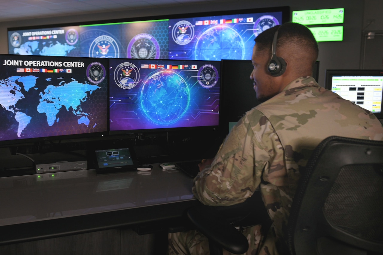 A Space Command service member sits and looks at monitors in a room.