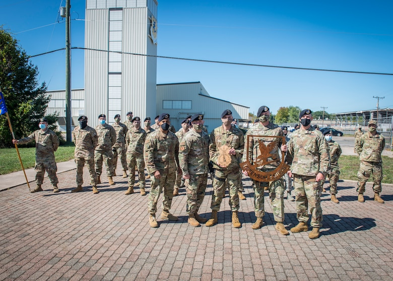 (Front, left to right) Col. Victor Moncrieffe, Air National Guard Chief of Security Forces, Lt. Col William Deme, 103rd Security Forces Squadron commander, Senior Master Sgt. James Reynolds, 103rd Security Forces Squadron Defender, Senior Master Sgt. Richard Marks, 103rd Security Forces Squadron Security Forces manager, and Chief Master Sgt. T.J. Hall, Air National Guard Security Forces career field manager, pose for a photograph with a formation of 103rd Security Forces Squadron Defenders following an award ceremony at Bradley Air National Guard Base, East Granby, Connecticut, Sept. 19, 2020. The squadron received the award for 2019 Air National Guard Outstanding Security Forces Unit of the Year, and Reynolds was named 2019 Security Forces Air Reserve Component Senior Noncommissioned Officer of the Year. (U.S. Air National Guard photo by Staff Sgt. Steven Tucker)