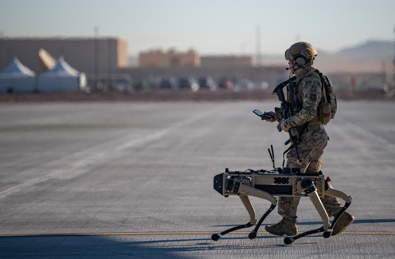 Tech. Sgt. John Rodiguez, 321st Contingency Response Squadron security team, patrols with a Ghost Robotics Vision 60 prototype at a simulated austere base during the Advanced Battle Management System exercise on Nellis Air Force Base, Nev., Sept. 3, 2020.