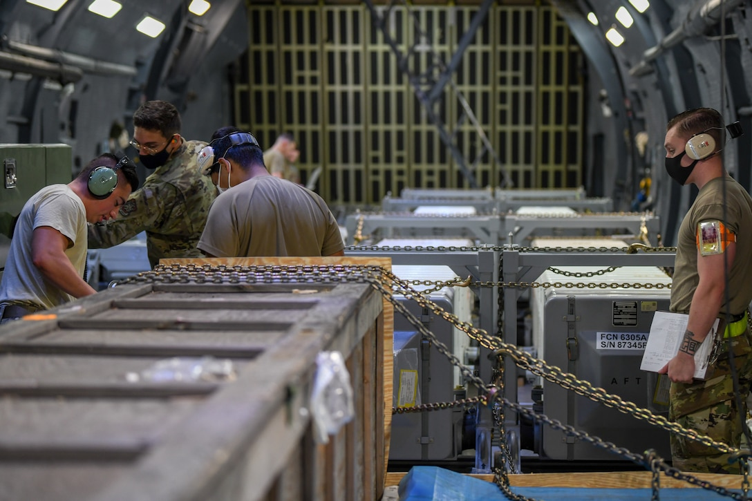 Airmen prepare for a cargo download aboard C-5M Supergalaxy