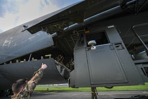 Airmen from the special handling shop direct a 60K operator for a cargo download