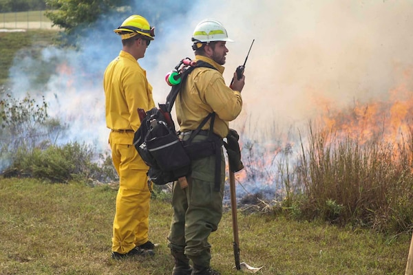 Chris Hanson, right, district fire management officer with the Kansas Forest Service, monitors a controlled burn with a Kansas National Guard student during the Wildland Firefighting Red Card Certification Course at the Great Plains Regional Training Center in Salina Sept. 17, 2020.