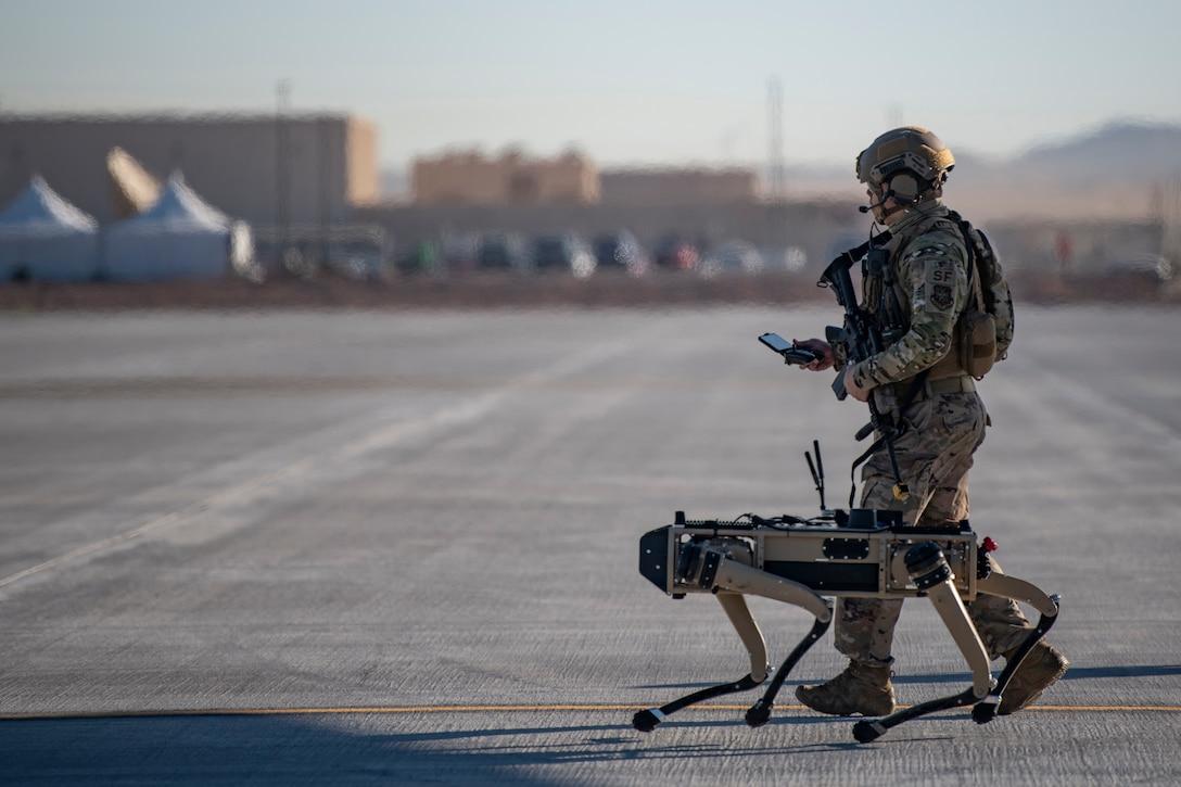 An airman walks beside a four-legged robot on a tarmac.