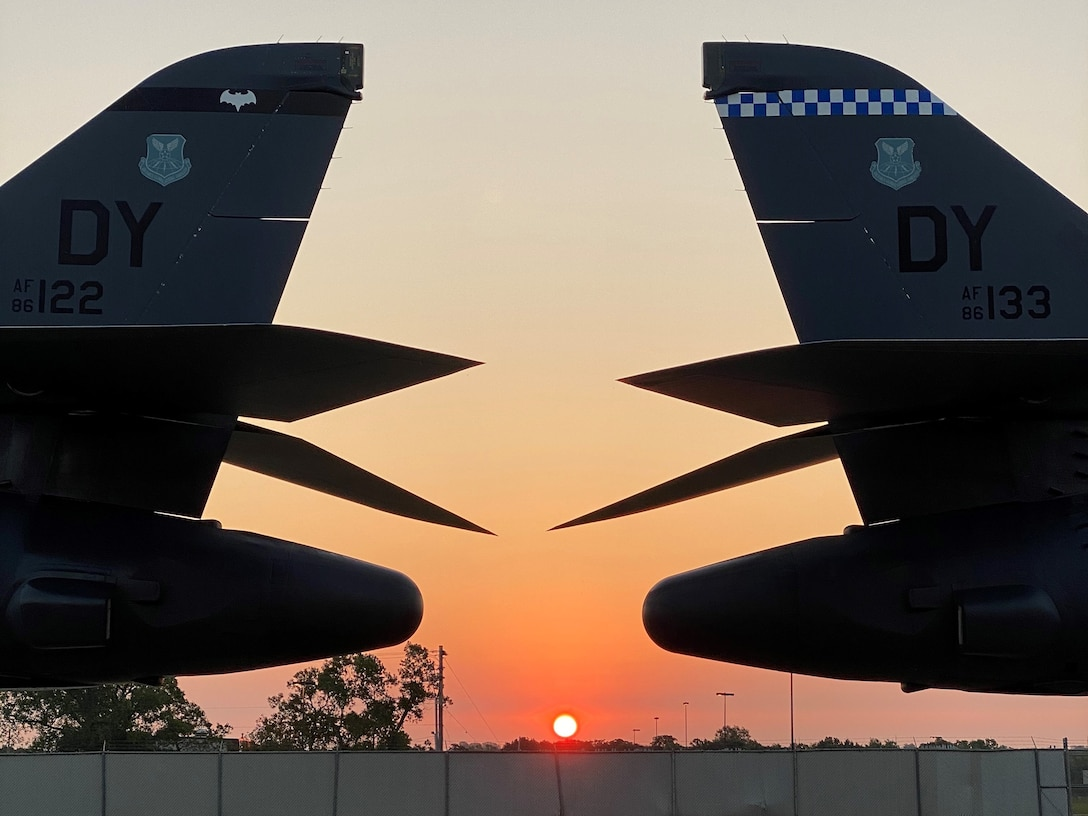 Two B-1B aircraft tails against sunrise.